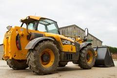Baubaggerlader im Bauernhofyard mit Scheune Lizenzfreie Stockbilder