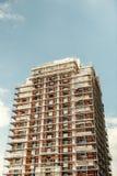 Baubaugerüst auf einem hohen Wolkenkratzergebäude Stockbild
