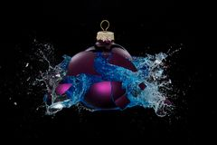 A bauble busting open releasing blue liquid Royalty Free Stock Photos