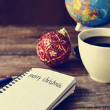 Bauble, cup of coffee, globe and text merry christmas Stock Photos
