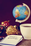Bauble, cup of coffee, globe and text seasons greetings. Closeup of a notebook with the text seasons greetings written in it on a rustic wooden table with some Royalty Free Stock Photos