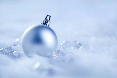 Bauble de prata do Natal na neve e no gelo da pele Fotos de Stock Royalty Free