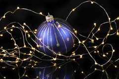 Bauble with fairy lights. Blue and silver bauble surrounded by fairy lights against a black background royalty free stock photos