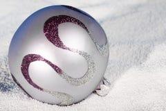Bauble macio do Natal do lilac sobre à neve. Foto de Stock Royalty Free
