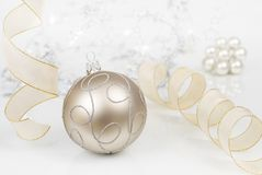 Bauble and ribbon. Christmas ornament on slightly reflecting surface, light colors, background out of focus stock photos
