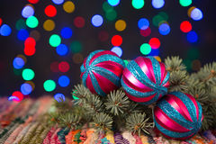 Baubles on Christmas lights background. Colorful baubles, spruce and Christmas lights background Royalty Free Stock Images