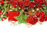 Baubles, golden garlands, christmas tree and red berries Stock Photos