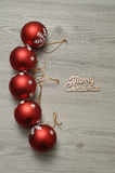 Baubles and merry christmas. A row of red baubles with a silver star and merry Christmas in gold text stock photography