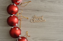 Baubles and merry christmas. A row of red baubles with a silver star and merry Christmas in gold text royalty free stock image