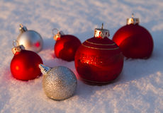Baubles in snow. Red and silver Christmas baubles in snow Royalty Free Stock Photo