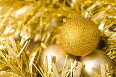 Baubles and tinsel. A close up of three christmas baubles nestled among some tinsel Royalty Free Stock Photography