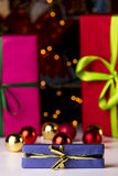 Baubles, twinkles and three wrapped gifts. Christmas bulbs and gifts wrapped in magenta and crimson in soft focus enhancing the sharp outlines of the blue box Royalty Free Stock Photo