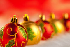 Baubles vermelhos dourados do Natal em uma fileira com luzes Imagens de Stock Royalty Free
