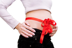 Bauch der schwangeren Frau mit rotem Farbband herum Lizenzfreies Stockfoto
