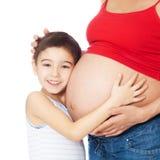 Bauch des lächelnden Jungenholdingmutter mit den Händen lizenzfreies stockbild