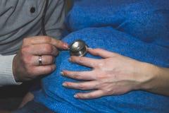 Bauch von Händen der schwangeren Frau und des Mannes mit Stethoskop Stockfotos