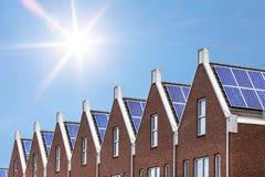 Bauen Sie eben Häuser mit den Sonnenkollektoren, die auf dem Dach befestigt werden Lizenzfreie Stockbilder