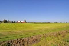 Bauernhäuser und Scheunen durch die Felder Stockbild