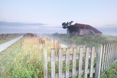 Bauernhaus bei nebelhaftem Sonnenaufgang Stockfoto