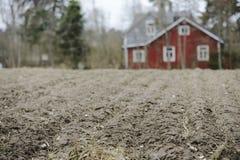 Bauernhaus in der Unschärfe hinter einem Feld Stockfotos