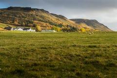 Bauernhaus mit grünem Feldeinfassungs-Gebirgszughintergrund Stockfotos