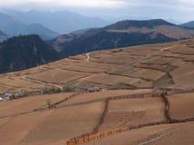 Bauernhof-Feld und ein Dorf am Berggebiet Lizenzfreies Stockfoto
