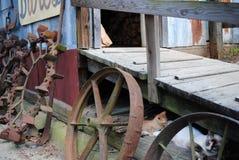 Bauernhof-Katze und Kätzchen mit alten Weinlese-Ackerschlepper-Rädern Stockfotografie