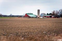Bauernhof mit Korn-Behältern und ein gepflogenes Feld im Vordergrund Stockfotos