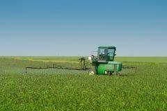 Bauernhof-Traktor-Sprüher auf dem Gebiet stockfoto