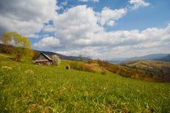 Bauernhof und Bergpanorama im Vorfrühling Stockbilder