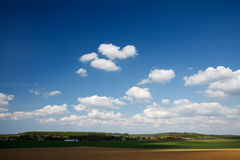Bauernhof unter hellem Himmel mit kleinen Wolken Lizenzfreies Stockfoto