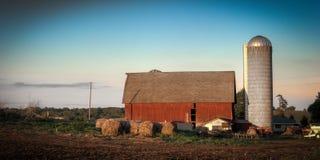 Bauernhoffeld und -gebäude Stockfoto