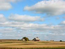 Bauernhofhaus und -felder unter blauem Himmel Stockfoto