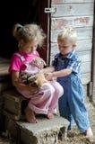 Bauernhofkinder und -kätzchen Stockfoto