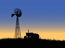 Bauernhoftraktor mit Windmühle Stockfotos