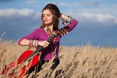Bauernmädchen, das ihr Haar repariert und eine Akustikgitarre auf dem Gebiet gegen blauen Hintergrund des bewölkten Himmels hält Lizenzfreies Stockbild