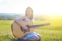 Bauernmädchen, das mit Akustikgitarre am Feld sitzt Stockfoto