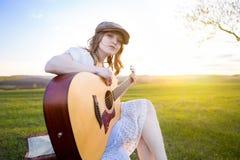Bauernmädchen, das mit Akustikgitarre am Feld sitzt Lizenzfreies Stockfoto
