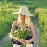 Bauernmädchen im Hut mit Blumen Stockfotografie