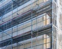 Baugerüst auf dem Oberteil eines großen Neubaus, mit einem Netz, zum von Passanten vor dem Fallen zu schützen wendet ein stockfoto