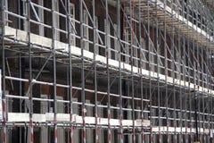 Baugerüst auf einem Gebäude, das Bauarbeit durchmacht Stockbild