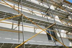 Baugerüst nahe einem Haus im Bau für externe Gipsarbeiten, hohes Wohngebäude in der Stadt, weiße Wand und Fenster, YE lizenzfreies stockfoto