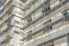 Baugerüst nahe einem neuen Haus, ein errichtendes Äußeres, eine Bau- und Reparaturindustrie, eine weiße Wand und ein Fenster, gel stockfotos