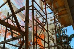 Baugerüst vor dem reparierten Gebäude wird mit BauSicherheitsnetz, Innenansicht, sonniger Herbsttag eingehüllt stockfotografie