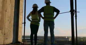 Baugewerbe: Teamwork-Konzept: Junge Ingenieurstellung hinter dem Betrachten einer Baustelle, eine Sicherheit tragend stock video footage
