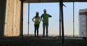 Baugewerbe: Teamwork-Konzept: Junge Ingenieurstellung hinter dem Betrachten einer Baustelle, eine Sicherheit tragend stock footage