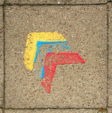 Bauhaus symbol paving stone. Paving stone with three painted arrow heads, yellow, blue and red symbolising bauhaus Stock Images