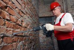 Bauherr in der Uniform, die mit einem Plugger arbeitet Lizenzfreies Stockbild