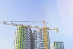 Bauhochhauskran auf dem Hintergrund von neuen grünen Gebäuden und von Blendenfleck Stockbilder