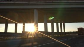 Bauholz-LKW transportiert hölzerne Klotz vor dem hintergrund einer modernen Brücke und eines Sonnenuntergangs, Frachttransportkon stock video